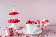 Coffee cup, white two tier serving tray full of multicolor sweet sprinkles sugar candy hearts and packing Valentine`s  Day gifts. Festive background.  Coffee cup Royalty Free Stock Photography