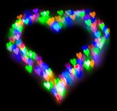 Colourful glitter formed a heart, bokeh in a shape of a heart. Festive background with de-focused colourful glitter formed a heart, bokeh in a shape of a heart Royalty Free Stock Image