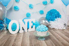 Festive background decoration for birthday celebration with gourmet cake, letters saying one and blue balloons in studio. Cake smash first year concept Royalty Free Stock Image
