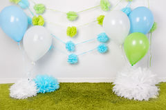 Festive background decoration for first birthday celebration or easter holiday with blue, green and white paper flowers, balloons. Fluffy rug on floor with Stock Photos
