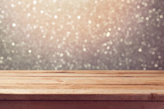 Festive background with empty wooden table over glitter bokeh lights Royalty Free Stock Images
