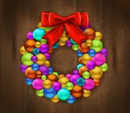 Christmas Wreath Wooden Background. Festive  background with fragment of wooden door decorated by wreath made of colorful christmas balls and red bow realistic Stock Image