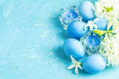 Festive background, Happy Easter greeting card in blue style. Blue easter eggs, candles and white hyacinth on blue concrete table surface background, copy space royalty free stock image