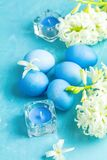 Festive background, Happy Easter greeting card in blue style. Blue easter eggs, candles and white hyacinth on blue concrete table surface background, copy space stock images