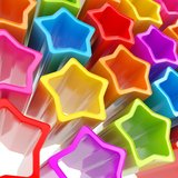 Festive background made of extruded colorful stars. Festive rainbow colored background made of extruded colorful glossy stars Stock Photography