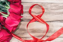 Festive background for March 8, World Women`s Day. Red roses and a red ribbon in the form of the figure eight, on a wooden backgro. Und royalty free stock images