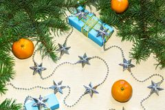 Festive background for the New Year and Christmas with a gerland of silver stars, boxes with gifts, tangerines and branches royalty free stock image