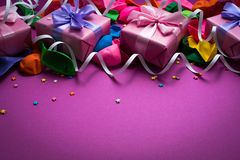 Festive background of purple material colorful balloons streamers confetti four boxes gift Top view flat lay copy space. Festive background of purple material stock photography