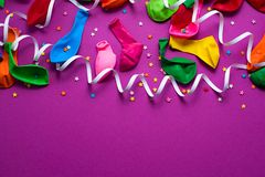 Festive background of purple material colorful balloons streamers confetti Top view flat lay copy space. Festive background of purple material colorful balloons stock photo
