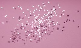 Festive background of silver star confetti on purple background royalty free stock image