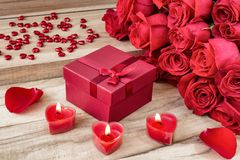 Festive background to the Valentine`s day. A bouquet of red roses, a gift box and a heart-shaped candle. On a wooden background royalty free stock photos