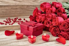 Festive background to the Valentine`s day. A bouquet of red roses, a gift box and a heart-shaped candle. On a wooden background royalty free stock photography