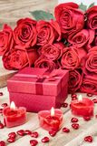 Festive background to the Valentine`s day. A bouquet of red roses, a gift box and a heart-shaped candle. On a wooden background stock images