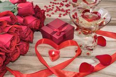 Festive background to the Valentine`s day. A bouquet of red roses, a gift box, a heart-shaped candle and a red ribbon with a heart. And two glasses painted for stock image