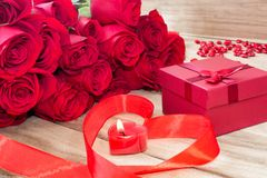 Festive background to the Valentine`s day. A bouquet of red roses, a gift box, a heart-shaped candle and a red ribbon with a heart. On a wooden background royalty free stock images