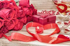 Festive background to the Valentine`s day. A bouquet of red roses, a gift box, a heart-shaped candle and a red ribbon with a heart. And two glasses painted for royalty free stock photos