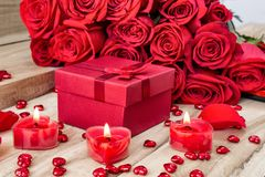 Festive background to the Valentine`s day. A bouquet of red roses, a gift box and a heart-shaped candle. On a wooden background. Festive background to the stock photo