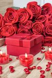 Festive background to the Valentine`s day. A bouquet of red roses, a gift box and a heart-shaped candle. On a wooden background stock photos