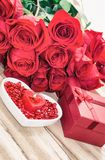Festive background to the Valentine`s day. A bouquet of red roses, a gift box, a heart-shaped plate and a heart-shaped candle. On a wooden background stock photography