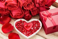 Festive background to the Valentine`s day. A bouquet of red roses, a gift box, a heart-shaped plate and a heart-shaped candle. On a wooden background stock photos