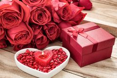 Festive background to the Valentine`s day. A bouquet of red roses, a gift box, a heart-shaped plate and a heart-shaped candle. On a wooden background stock photo