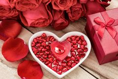 Festive background to the Valentine`s day. A bouquet of red roses, a gift box, a heart-shaped plate and a heart-shaped candle. On a wooden background royalty free stock images