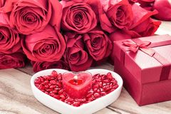 Festive background to the Valentine`s day. A bouquet of red roses, a gift box, a heart-shaped plate and a heart-shaped candle. On a wooden background royalty free stock photos