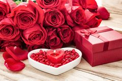 Festive background to the Valentine`s day. A bouquet of red roses, a gift box, a heart-shaped plate and a heart-shaped candle. On a wooden background royalty free stock photo
