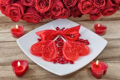 Festive background to the Valentine`s day. A bouquet of red roses, two heart-shaped candies and a heart-shaped candle. On a wooden background royalty free stock photo
