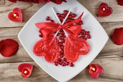 Festive background to the Valentine`s day. A bouquet of red roses, two heart-shaped candies and a heart-shaped candle. On a wooden background stock photo