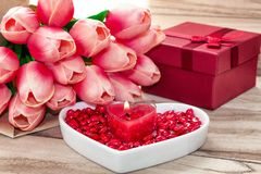 Festive background to the Valentine`s day. A bouquet of tulips, a gift box, a heart-shaped plate and a heart-shaped candle. On a wooden background royalty free stock images
