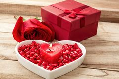 Festive background to the Valentine`s day. Flower rose, gift box, a heart-shaped plate and a heart shaped candle. On a wooden background stock images