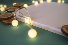 Festive background, white paper, a place for texts,. Christmas garland, lanterns, warm light, tree cuts stock photo