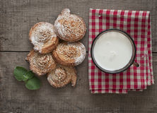 Festive baking and milk. Festive sweets, puff cookies with sesame seeds, sugar candies and milk on gingham table cloth Stock Images