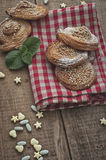 Festive baking. Festive sweets, puff cookies with sesame seeds and sugar candies on gingham table cloth Royalty Free Stock Photography
