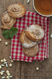 Festive baking and tea. Festive sweets, puff cookies with sesame seeds, sugar candies and cup of tea on gingham table cloth Stock Photos