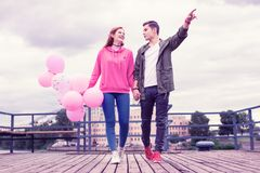 Active excited guy showing something to interested happy girl stock images