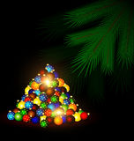 Festive balls and bunch of tree. Dark abstract room, multicolored Christmas balls on the floor and the green branch of the large tree Royalty Free Stock Photos