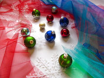 Festive balls and snowflakes on the Christmas tree. Colorful fabric-mesh around as background Stock Photography