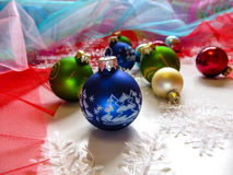 Festive balls and snowflakes on the Christmas tree. Multicoloured fabric-mesh around as background Royalty Free Stock Image