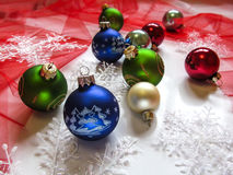 Festive balls and snowflakes on the Christmas tree. Red fabric-mesh around as background Royalty Free Stock Images