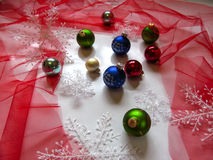 Festive balls and snowflakes on the Christmas tree. Red mesh around as background Stock Photos
