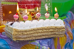 A festive banana cake with cream and candles five bells for a birthday on a picnic on a festive background. stock photography