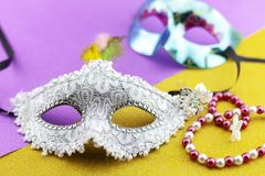 A festive,Beautiful white mardi gras or carnival mask on beautiful colorful paper background.  stock images