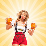 Festive beers. Beautiful surprised sexy woman wearing red jumper shorts with suspenders as traditional dirndl, holding two beer mugs on colorful abstract Royalty Free Stock Photography