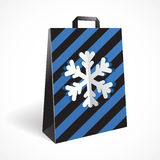 Festive black striped paper-bag with cut out snowflake Royalty Free Stock Images