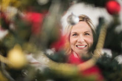 Festive blonde hanging bauble on christmas tree Stock Photos