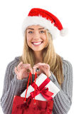 Festive blonde holding christmas gift and bag Stock Photos