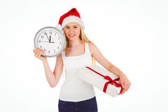 Festive blonde holding a clock and gift Royalty Free Stock Image
