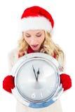 Festive blonde holding large clock Royalty Free Stock Photo